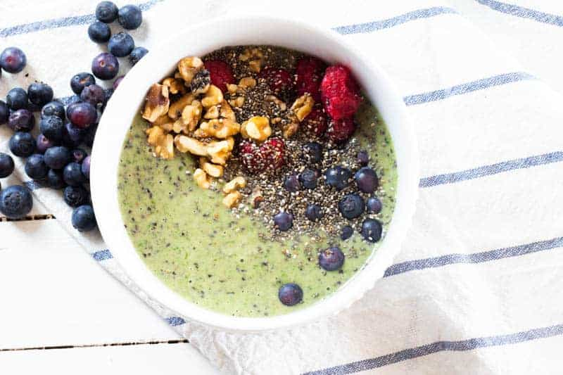 blueberry smoothie bowl with spinach walnuts raspberries and chia seeds in white bowl