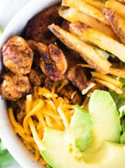 southwest chicken, avocado slices, shredded cheese, and French fries in white bowl