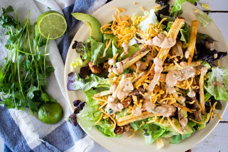 large southwest chicken salad on tan plate with lime and cilantro