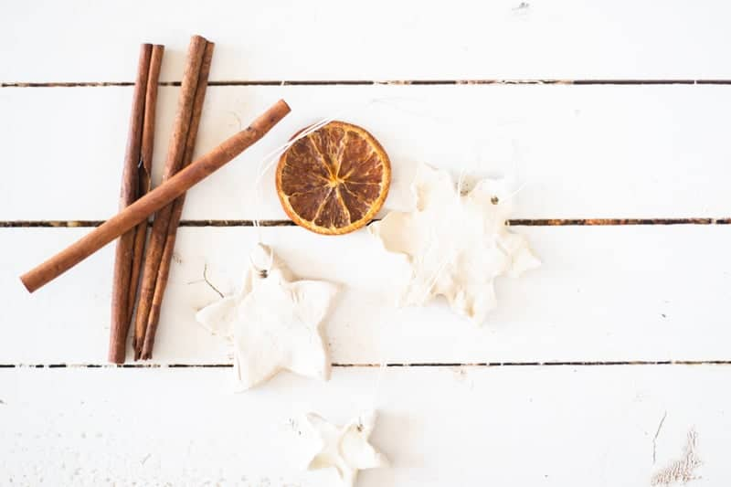 diffuser ornaments on white ship lap with cinnamon sticks and dried orange slice