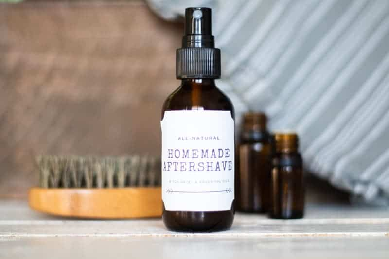 homemade aftershave spray for men with brush glass bottles and towel on white shiplap