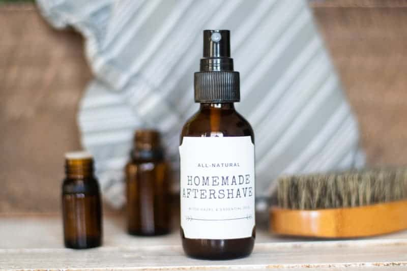 diy aftershave spray with essential oil bottles and beard brush in background