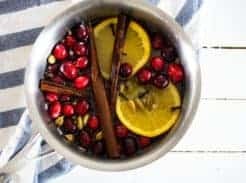 cranberries cinnamon sticks and orange slices in saucepan