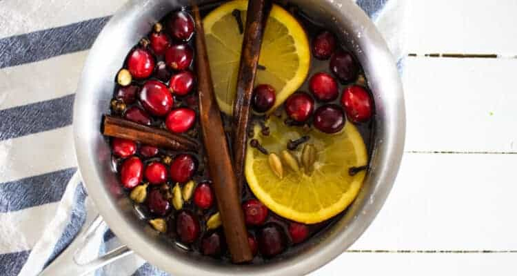 cranberries cinnamon sticks and orange slices in saucepan