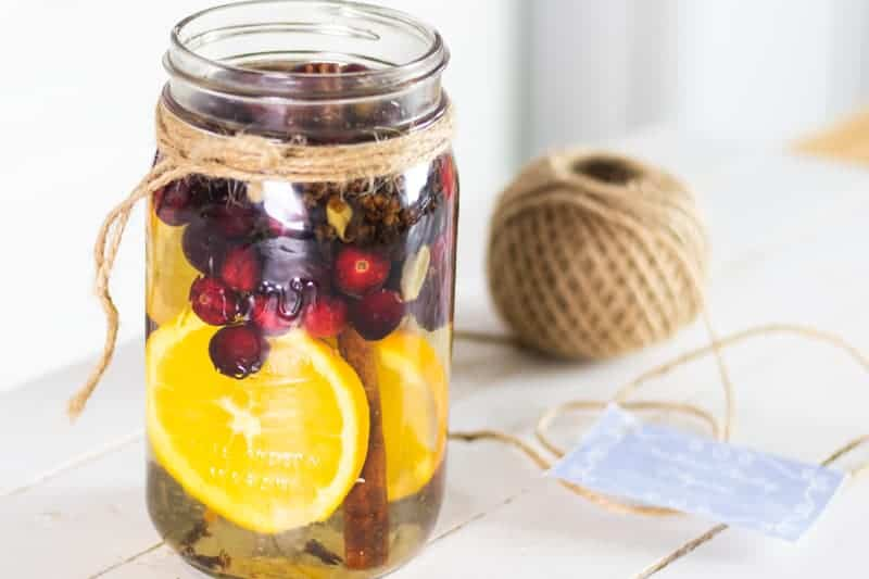 cranberries orange slices fresh herbs and cinnamon sticks in mason jar with water for stovetop potpourri