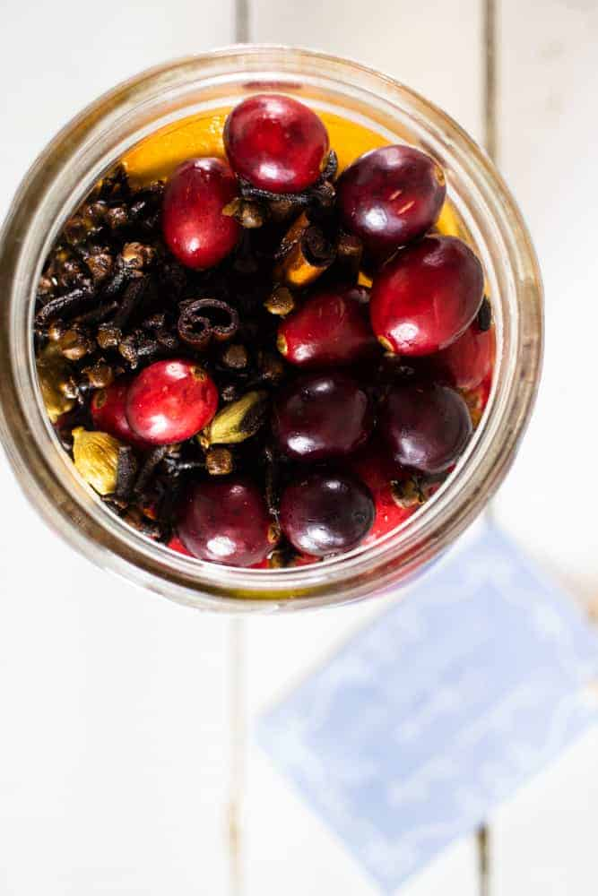 overhead shot of mason jar full of cranberries, cloves, and orange slices