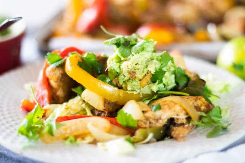 chicken fajita salad on white plate topped with guacamole and cilantro