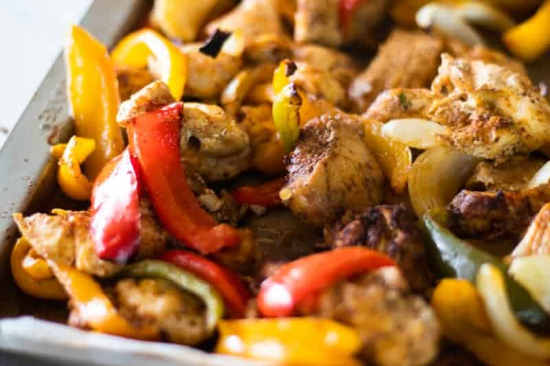 chicken fajita sheet pan with bell peppers onions and homemade seasoning on baking dish