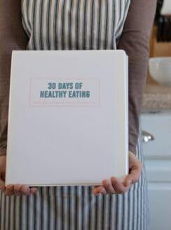 hands holding cookbook in kitchen