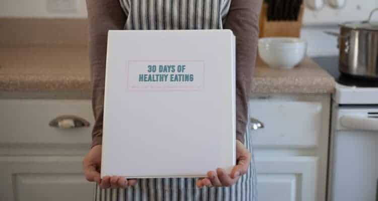 hands holding cookbook in kitchen