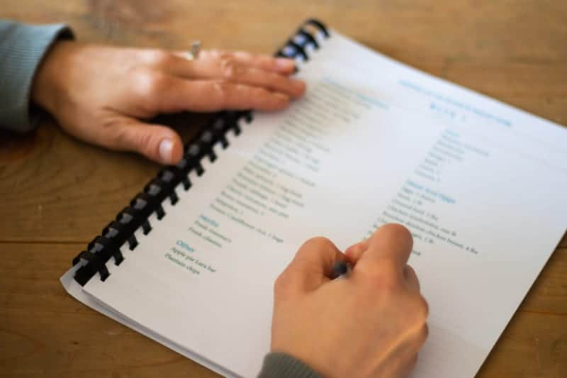 filling out grocery list for whole 30 meal planning on wooden table