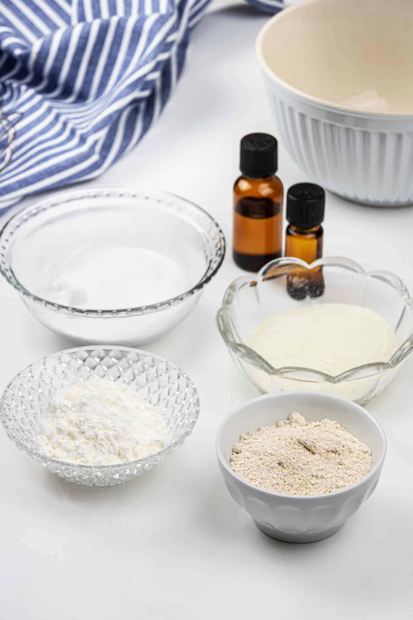 ingredients to oatmeal bath in small glass bowls with essential oils.