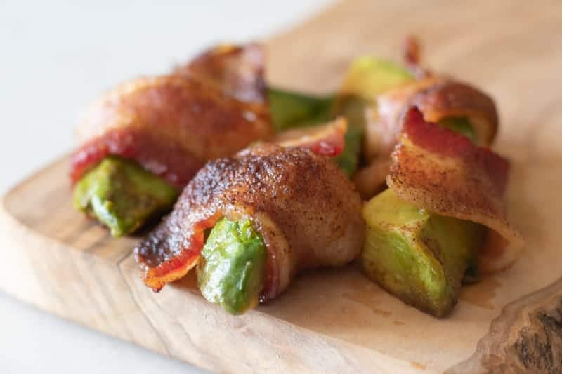 bacon wrapped avocado fries on wood cutting board