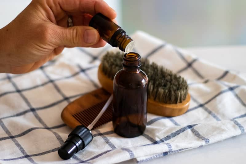 Adding essential oils to the diy aftershave bottle.
