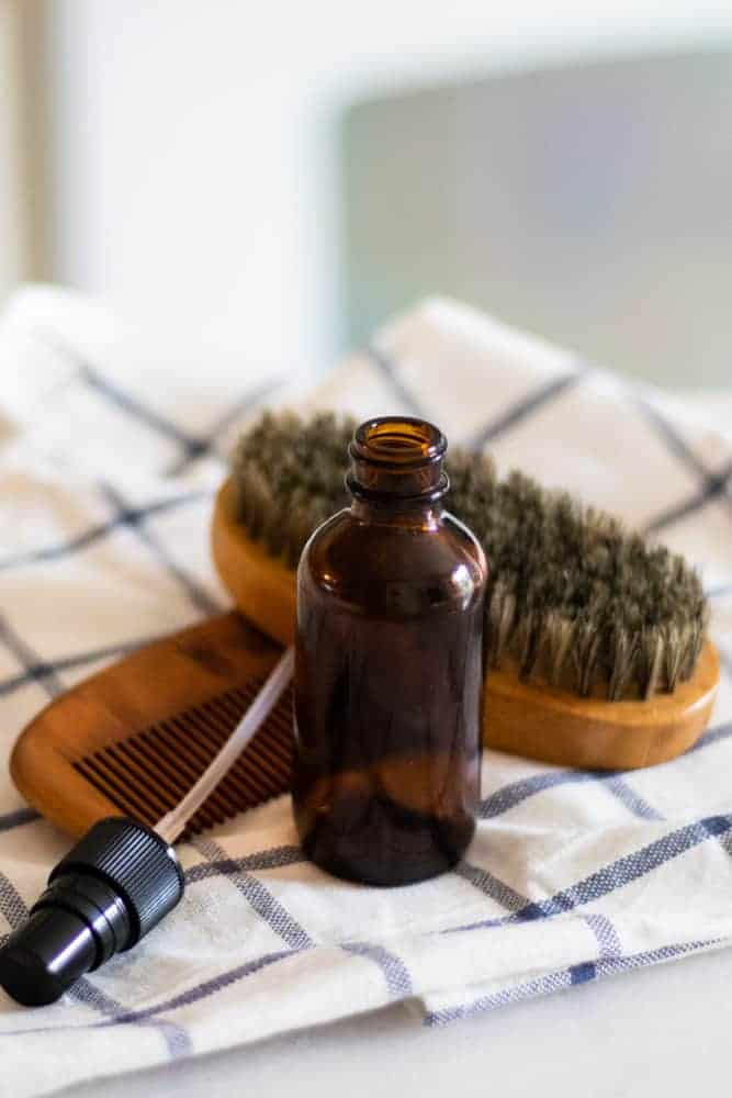 homemade aftershave in amber glass spray bottle with a wooden beard comb and brush