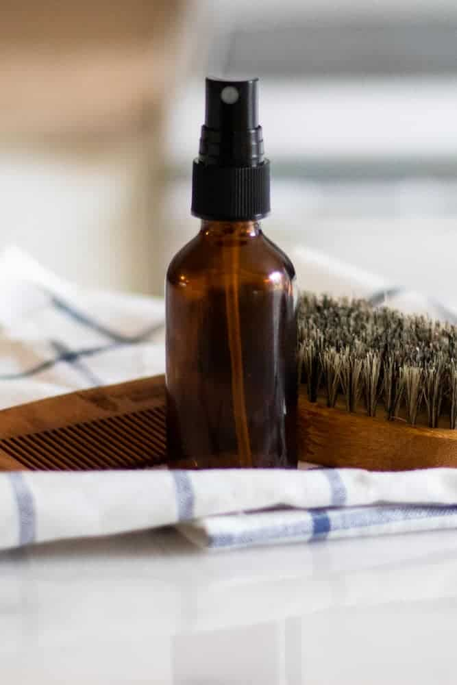 Homemade aftershave spray on white and blue towel in front of beard grooming supplies.