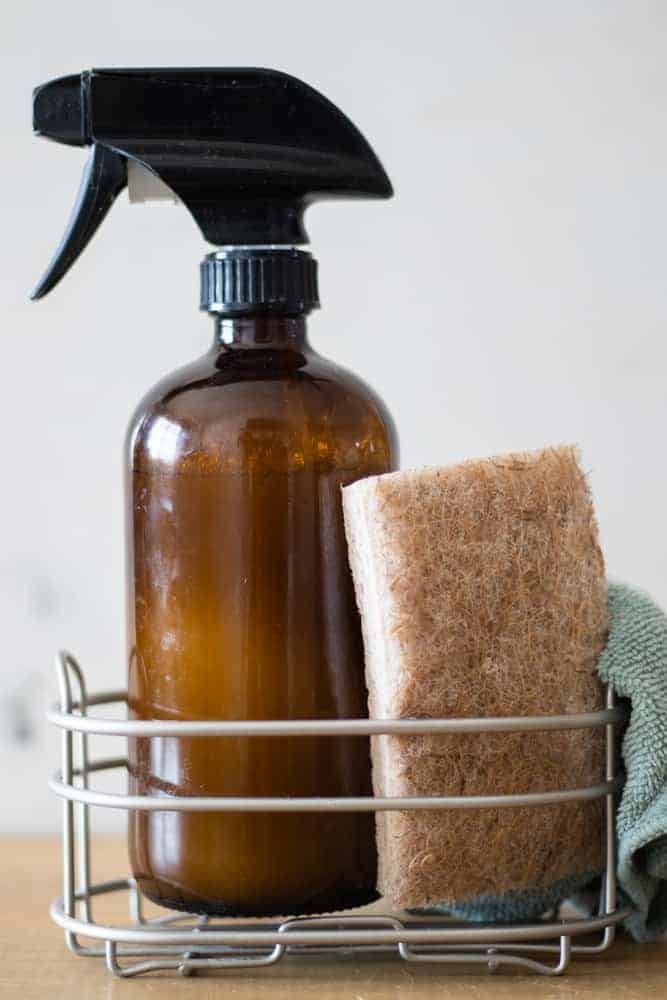 DIY granite countertop cleaner in an amber spray bottle on a metal rack with a scrub brush and micro-fiber towel.