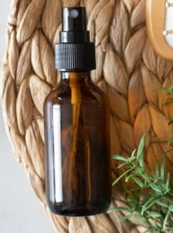 amber spray bottle of hair spray with rosemary and tan brush