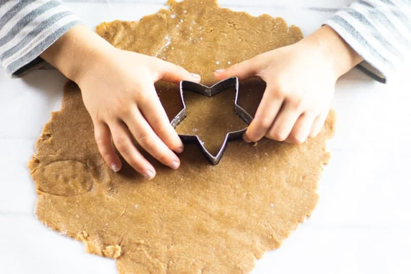 hands pressing star shaped cookie cutter into rolled out dough