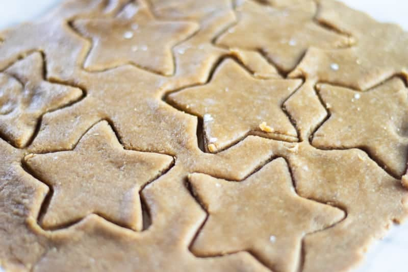 paleo Christmas sugar cookie dough rolled out with star cookie cutter shapes