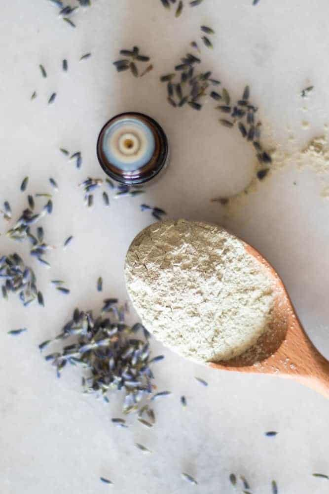 powder clay for face mask on wooden spoon with lavender springs and an essential oil bottle around it