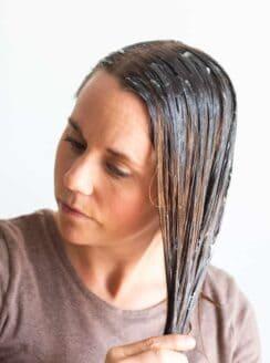 women massaging hair mask into hair