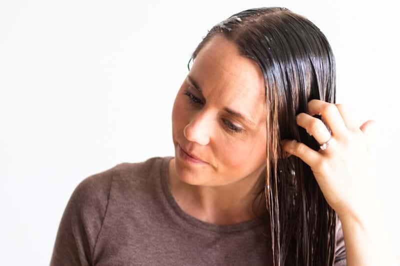 women applying hair mask to long brown hair