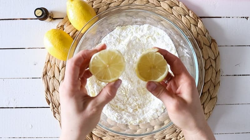 squeezing fresh lemon juice into glass bowl of dry ingredients
