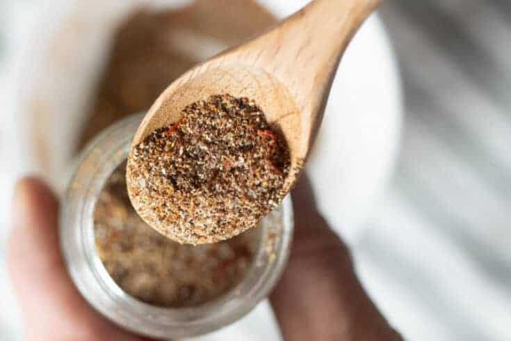 wooden spoon pouring taco seasoning in spice jar