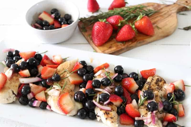 grilled chicken with berry salsa on white plate on white shiplap.
