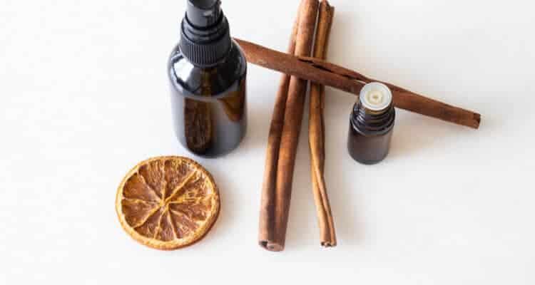 amber glass bottle. cinnamon sticks, orange slice, and essential oils on white marble