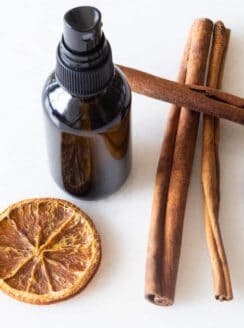 diy hand sanitizer spray in glass bottle with cinnamon sticks and orange slices on white table