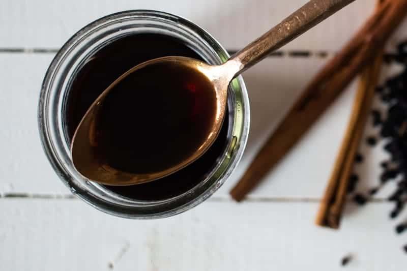 elderberry syrup on gold spoon over mason jar