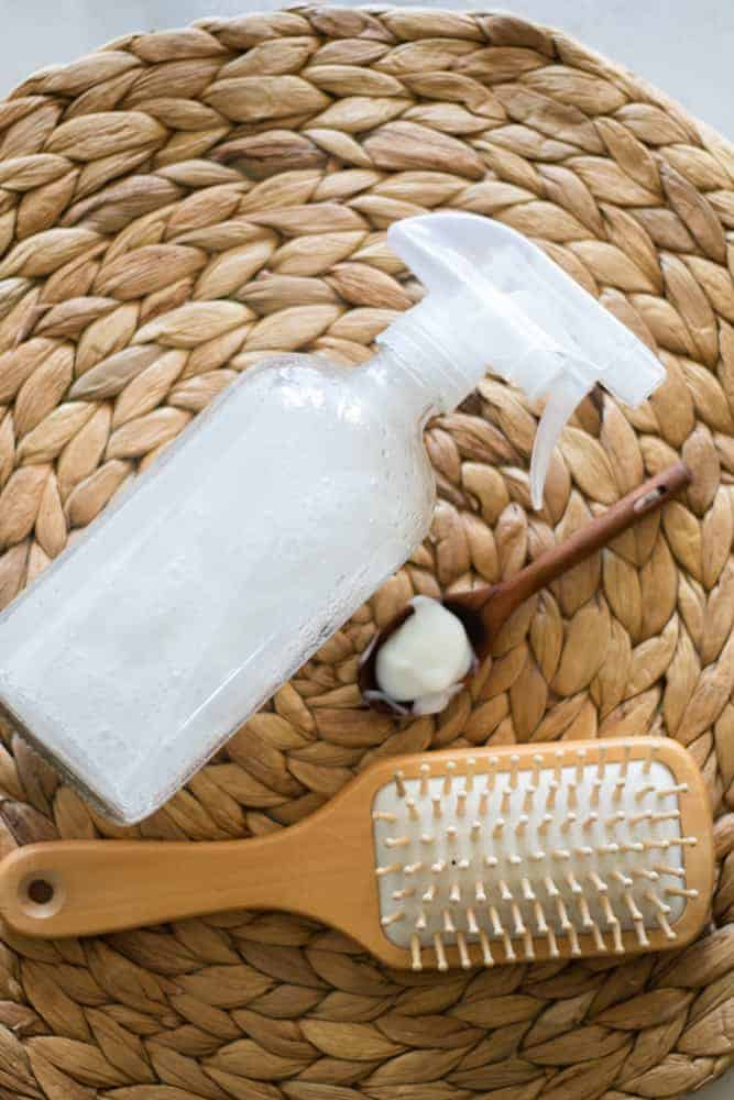 glass spray bottle with heat protection spray next to a brush and tablespoon on round woven mat