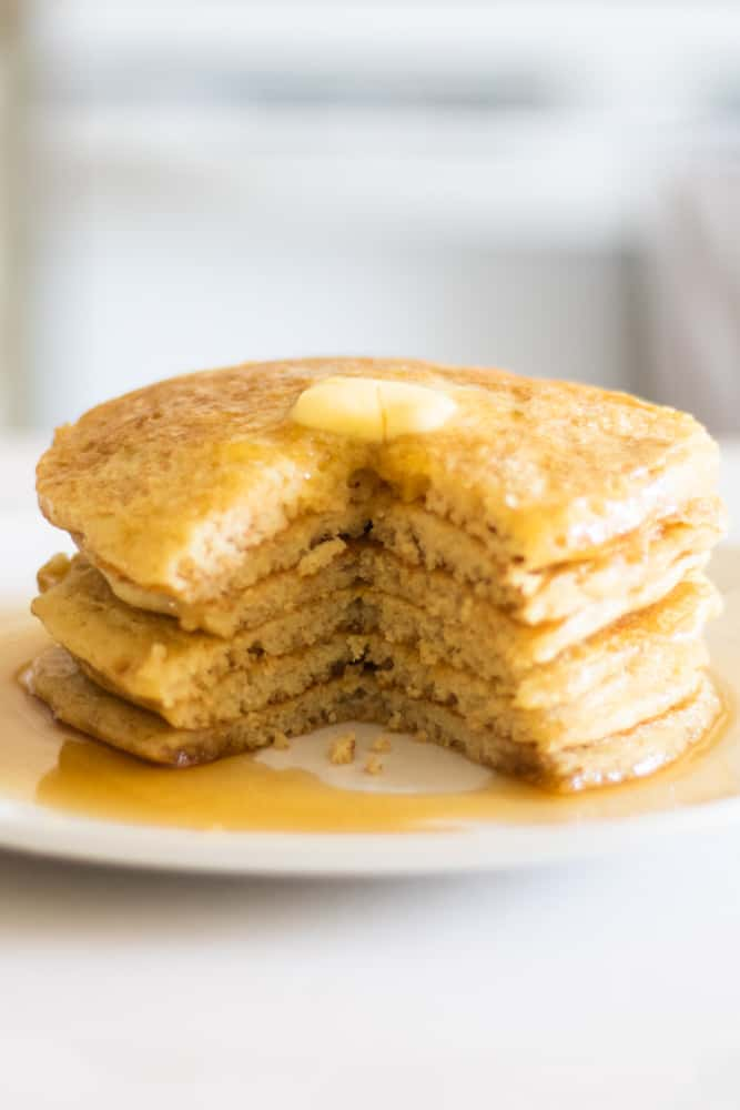 tall stack of pancakes with a bite taken out of it.