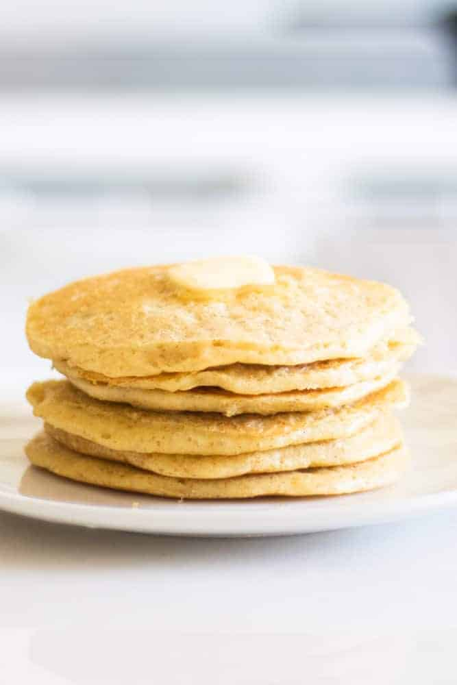 stack of sourdough pancakes on white plate with a chunk of butter