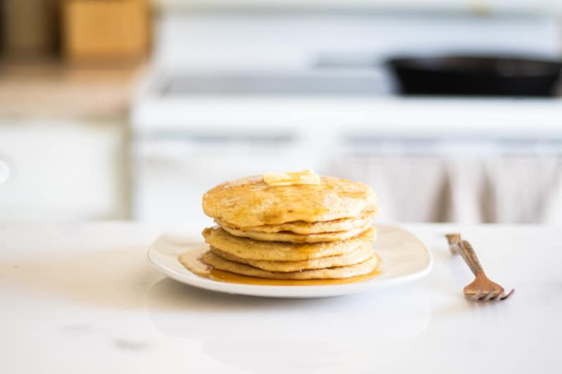 stack of pancakes on white marble counter with brass fork