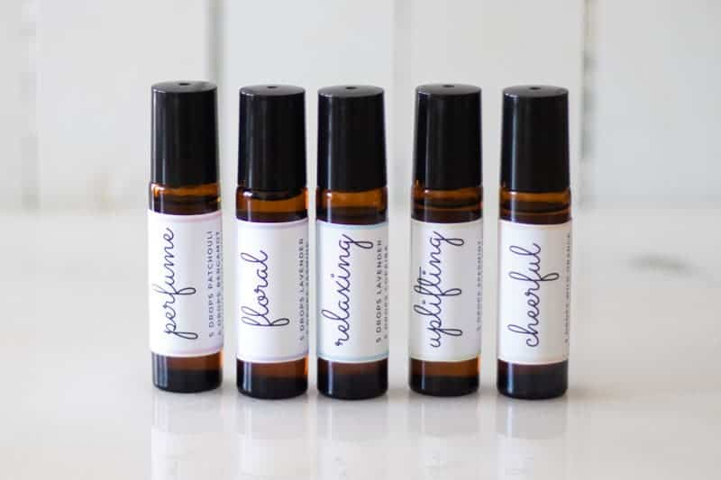 amber essential oil roller bottles with black lids and white labels on white marble countertop
