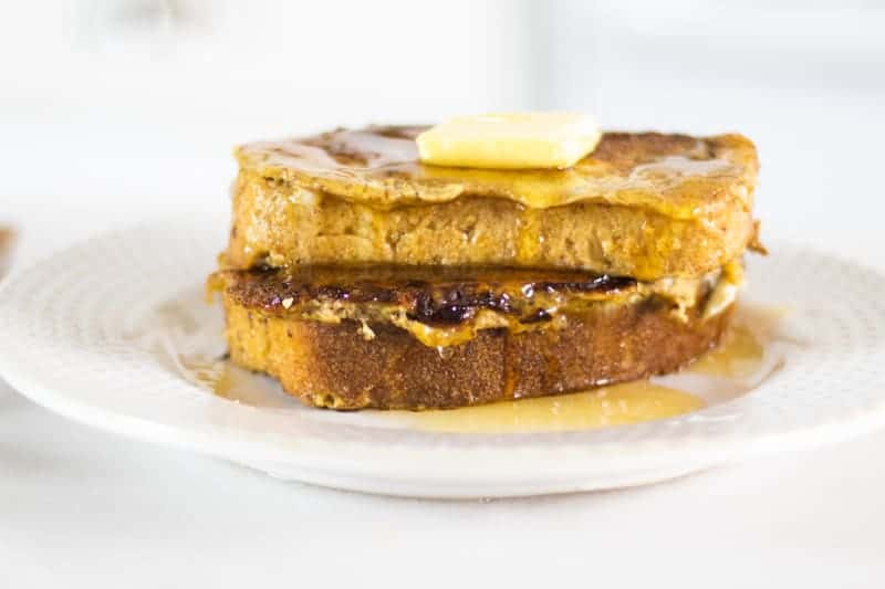 thick sliced sourdough French toast with butter maple syrup on white decorative plate