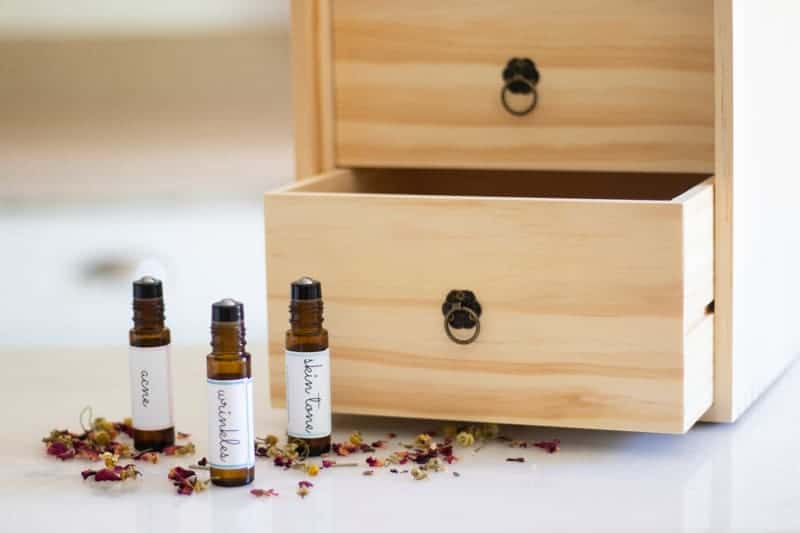 roller bottles in front of wooden essential oil storage box