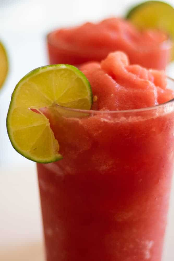 healthy watermelon slushy with fresh lime in a tall glass