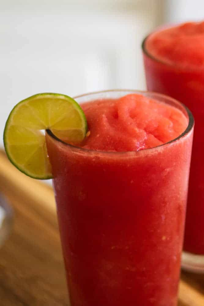 watermelon slushy in glass with lime slice
