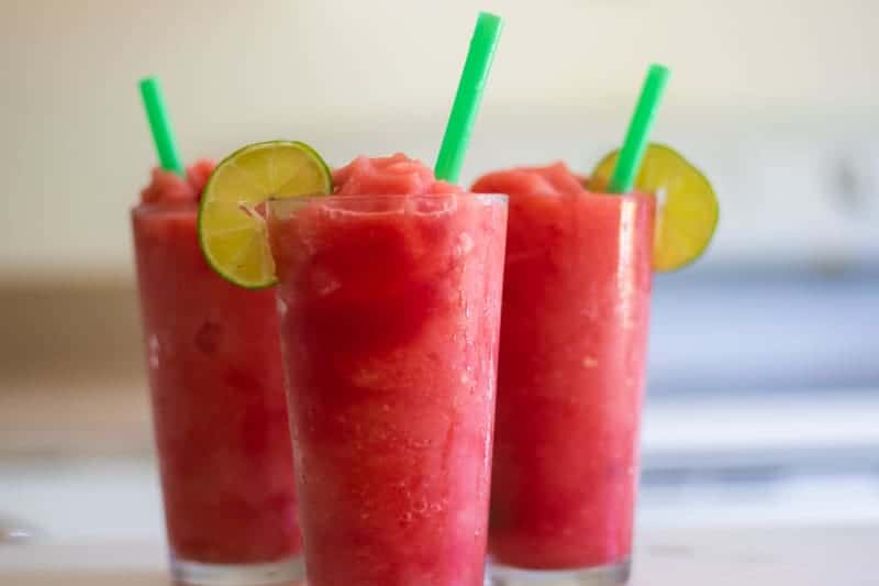 three red watermelon slushies with lime slices and green straws