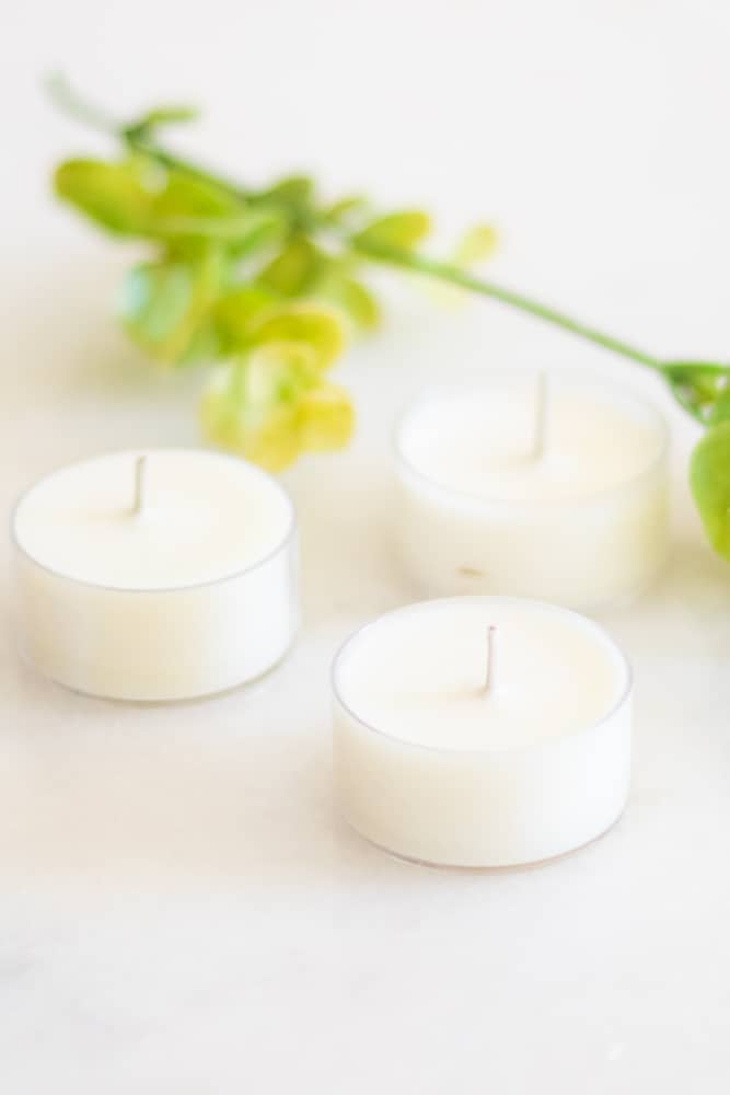 white citronella candles on white marble with greenery in background