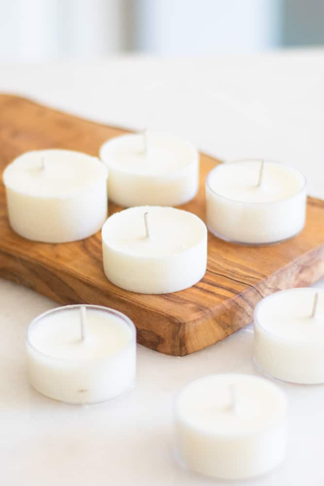 homemade citronella candles on wooded cutting board.