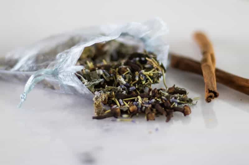 dried herbs in mesh bag with cinnamon sticks next to it