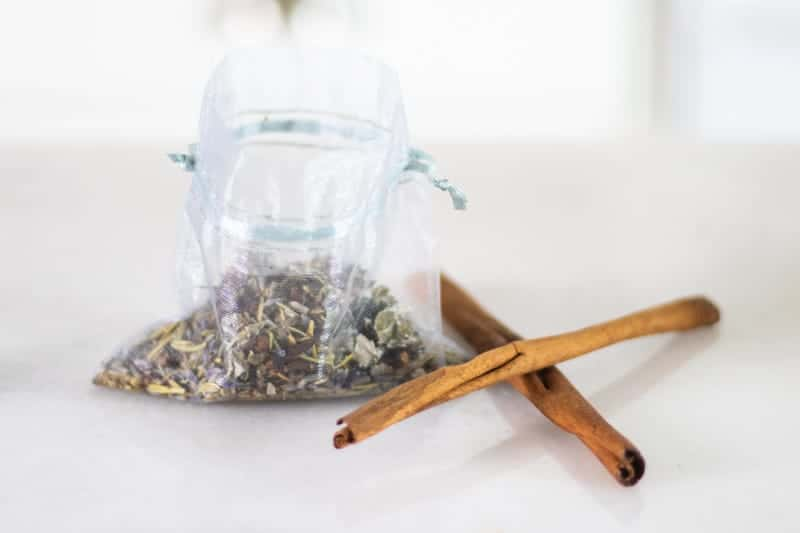 dried herbs in mesh bag with two cinnamon sticks next to it