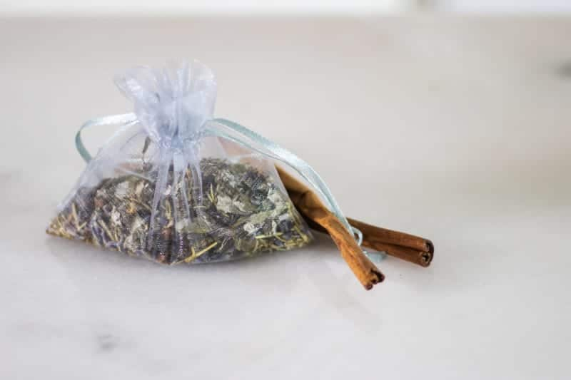 mesh bag of moth repellent with dried herbs on white marble