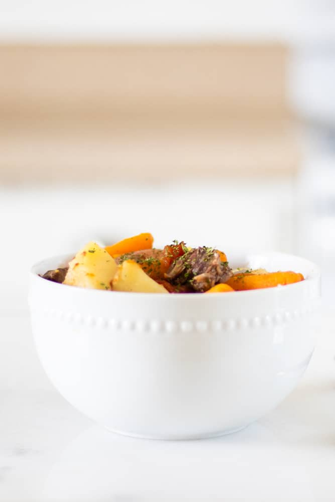 white bowl of homemade beef stew recipe with decorative greens sprinkled on top.