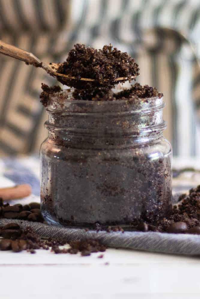 spooning homemade coffee body scrub from glass jar.